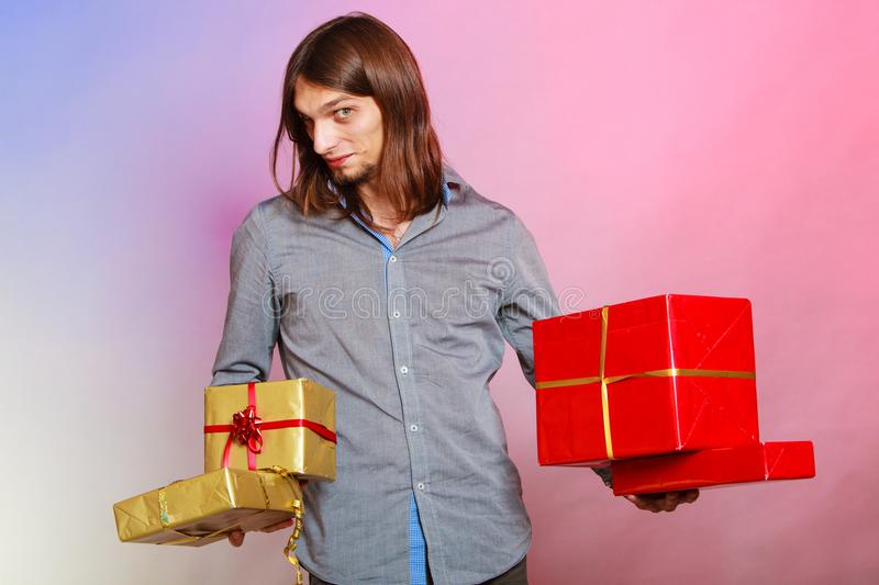 Guy with many presents gift boxes. Holiday, xmas winter time season and special occasion. Young handsome stylish man holding a lot of presents gifts boxes stock photo