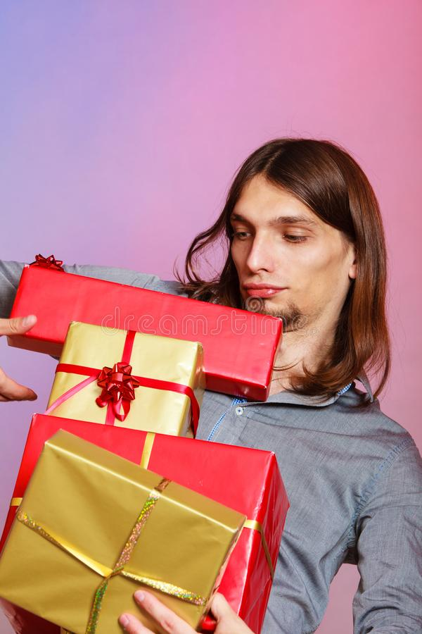 Guy with many presents gift boxes. Holiday, xmas winter time season and special occasion. Young handsome stylish man holding a lot of presents gifts boxes stock images