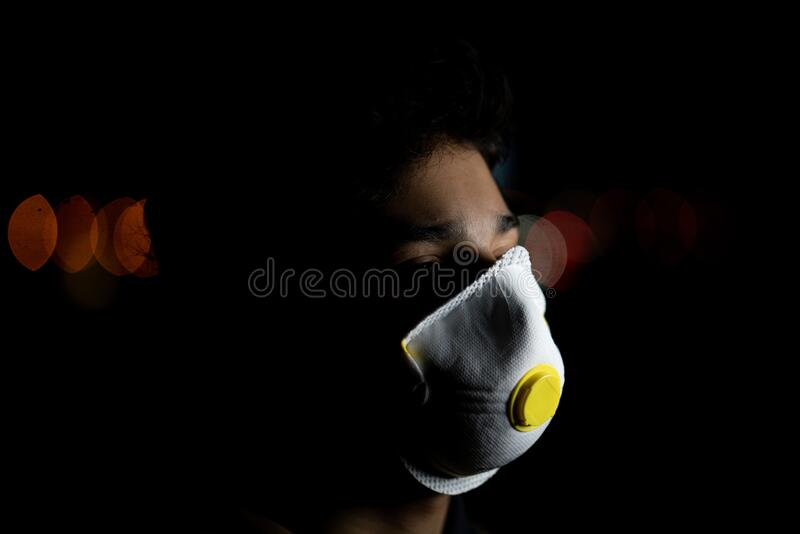 Guy with mask on city night street stock photography