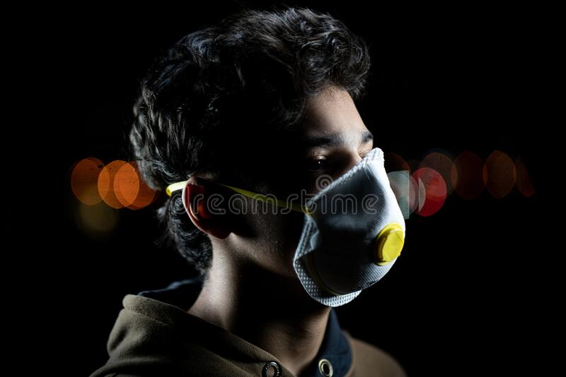 Guy with mask on city night street royalty free stock images