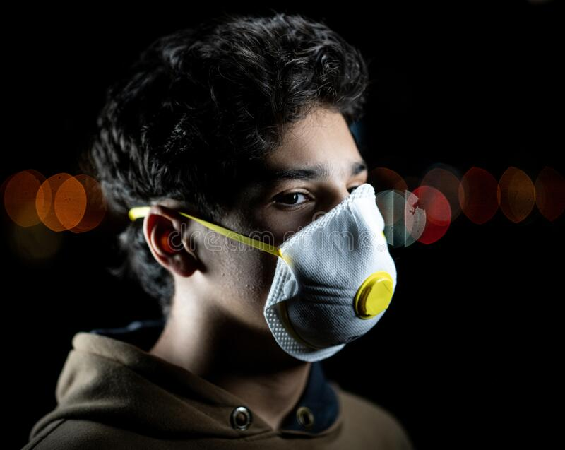 Guy with mask on city night street stock image