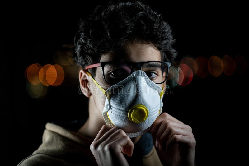 Guy with mask on city night street stock images