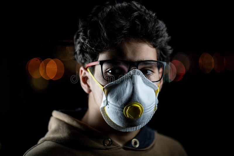 Guy with mask on city night street stock photo