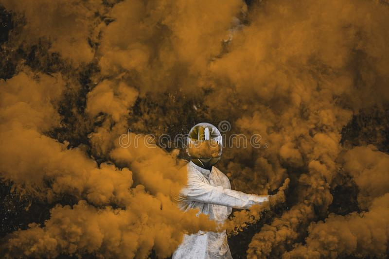 Guy in mask standing in between orange brown smoke bombs royalty free stock photography