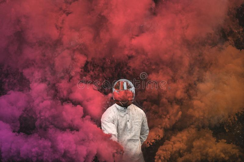 Guy in mask standing in between pink, purple and orange smoke bombs stock images