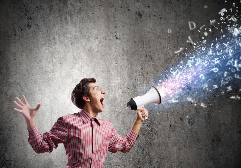 Guy with megaphone. Young man in casual screaming megaphone stock image