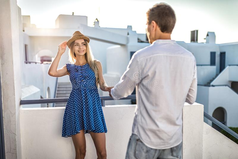 Guy or man flirts with girl holding her hand. First date, romantic meeting greece summer at sunse royalty free stock photo