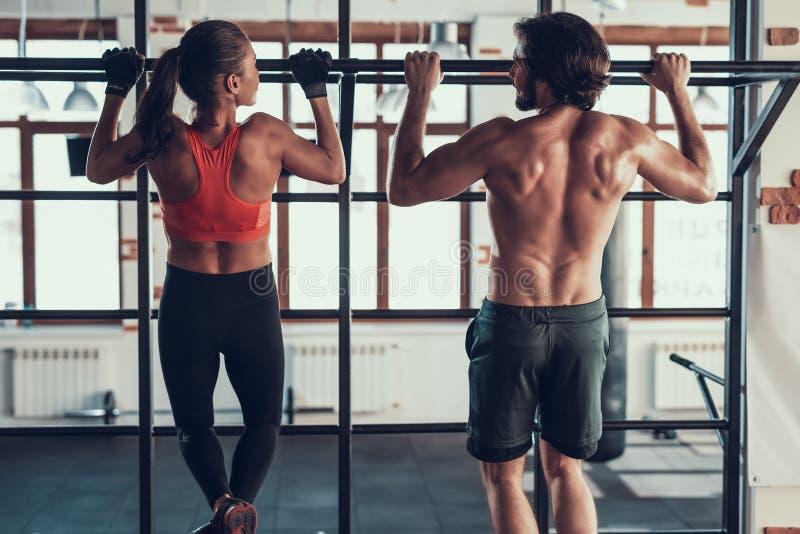 Guy And a menina de A que está fazendo a tração levanta no Gym fotos de stock royalty free
