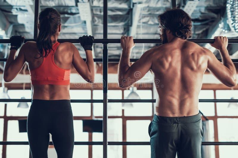 Guy And a menina de A que está fazendo a tração levanta no Gym fotos de stock