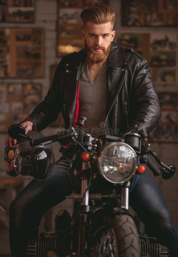 Guy in motorbike repair shop stock photo