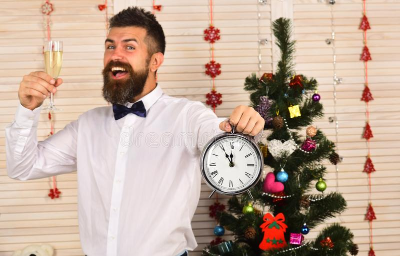 Guy near Christmas tree on wooden wall background. stock photo