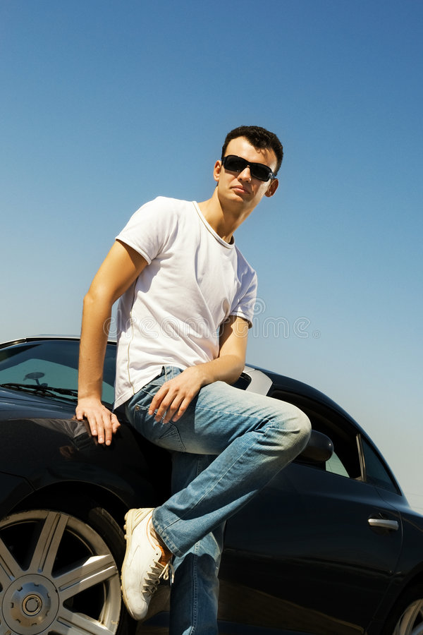 Guy near the sport car. Young handsome guy near the sport car stock photography