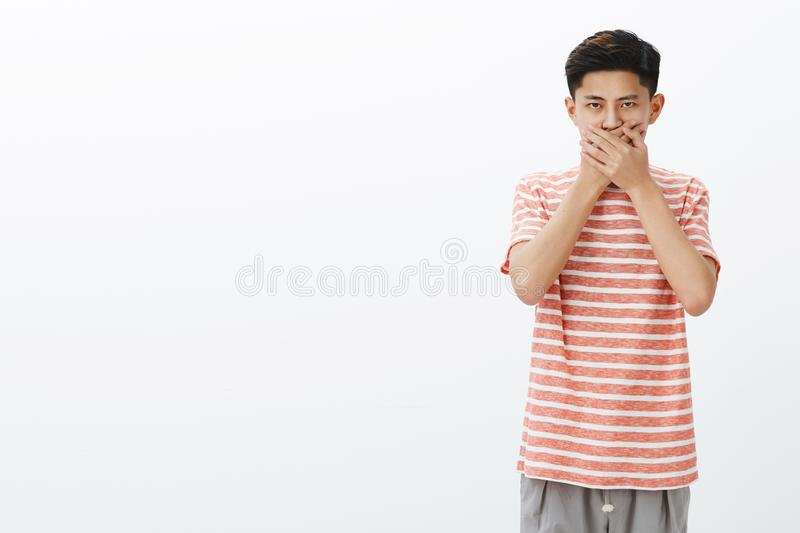 Guy not in mood to speak. Portrait of serious-looking intense young asian teenager in striped t-shirt pressing palms to royalty free stock images