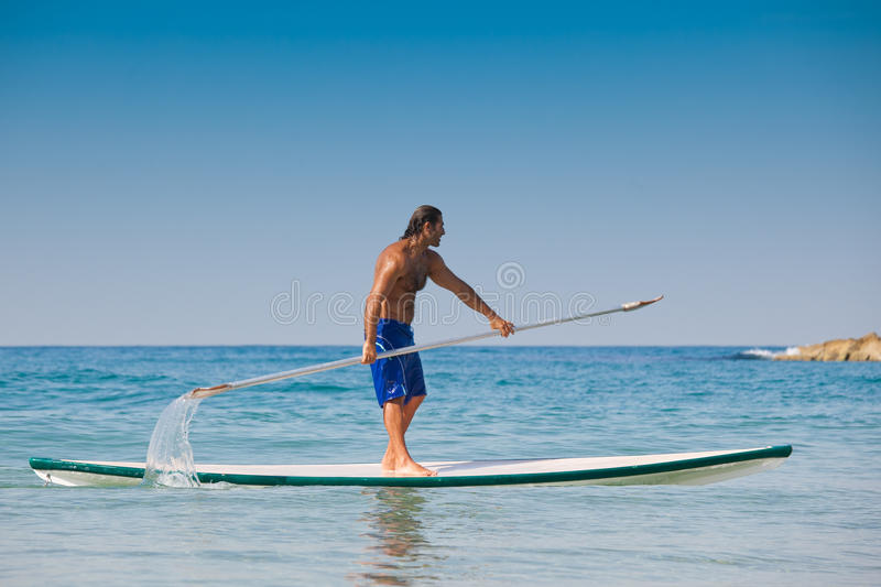 Download The Guy With An Oar On A Surfboard. Stock Photo - Image: 23549780