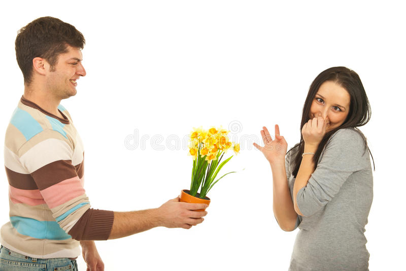Guy offering flowers to picky woman. Guy offering daffodil flower to a picky women who making faces and pinching her nose to avoid the odor of flower isolated on stock photography