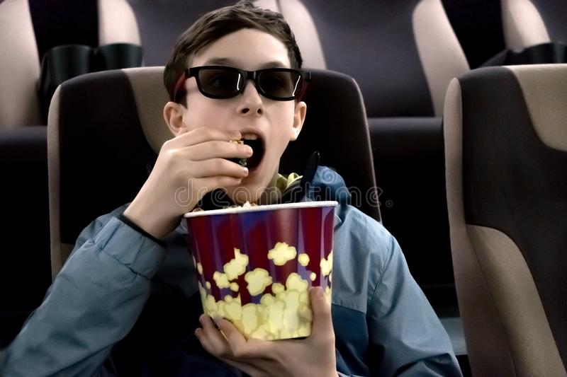 The teenager in the cinema in 3D glasses with popcorn in their hands. The guy opened his mouth and watches the movie in surprise stock images