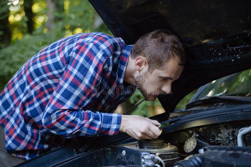 The guy looks at the car engine royalty free stock image