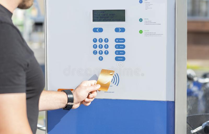 Guy paying for bike with credit card, using modern contactless system. At rental station outdoor stock images