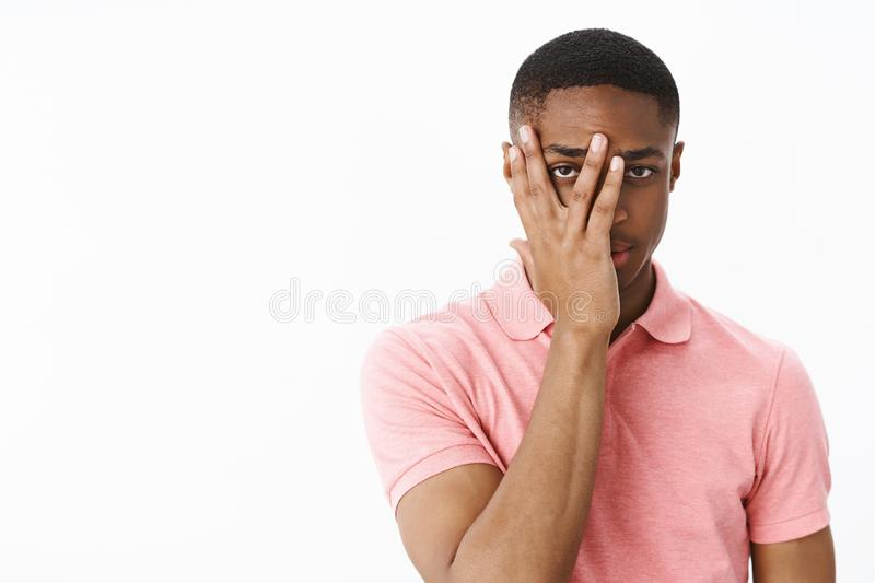 Guy peeking at camera through fingers on face looking serious and interested what happening, posing curious in pink polo royalty free stock images