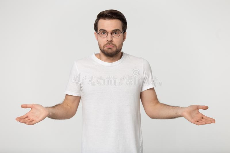 Guy in perplexity shrugged his shoulders studio shot. Confused young man wearing white t-shirt glasses being in perplexity, guy shrugged his shoulders look at stock photography