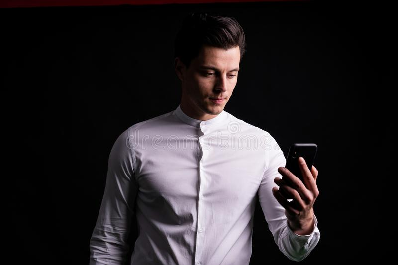 The guy with the phone in hand taking a selfie or talking with friends. Black background in the Studio stock photos