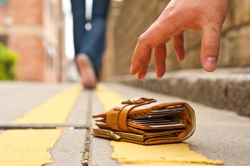Guy picking up a lost a lost purse/wallet. On the street stock photos