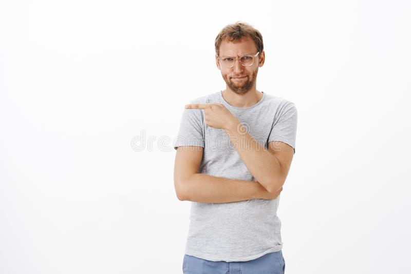 That guy me off. Portrait of intense bothered and irritated good-looking adult man with bristle in glasses stock photo