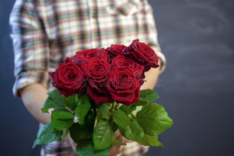 The guy in the plaid shirt holds a bouquet of red roses in his hand, focus on flowers. stock photography