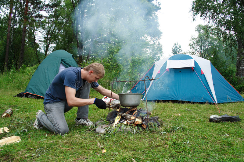 Guy plants a fire. Image of the guy planting a fire and tents on the nature stock image