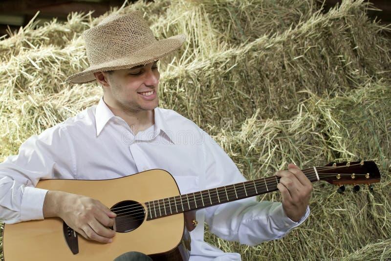 Guy Playing Country e música ocidental na guitarra dentro foto de stock royalty free