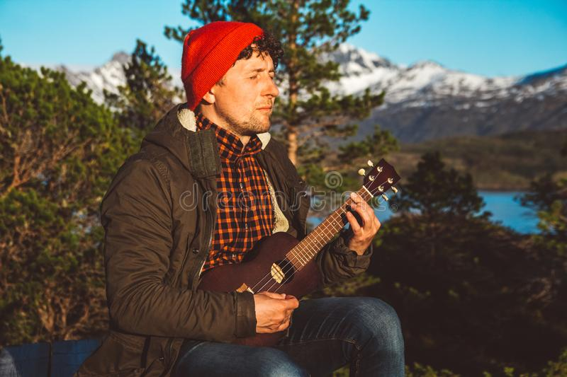 Guy playing guitar against the background of mountains, forests and lakes, wear a shirt and a red hat. Relaxing and royalty free stock images