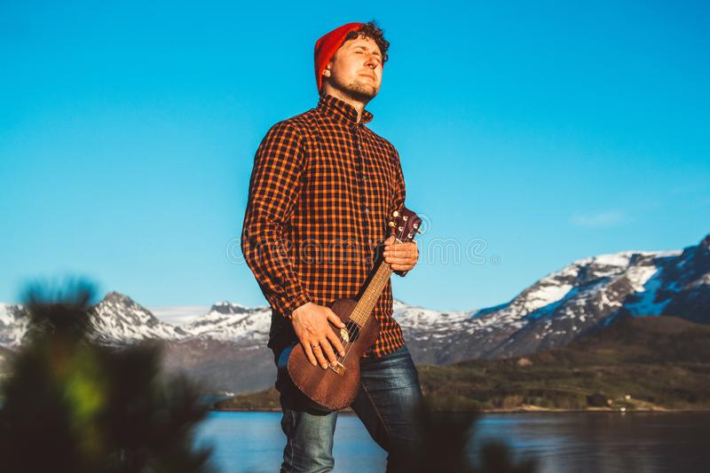 Guy playing guitar against the background of mountains, forests and lakes, wear a shirt and a red hat. Relaxing and royalty free stock photography