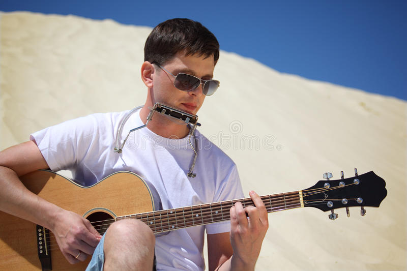 Guy plays guitar and lip accordion sitting on san stock image