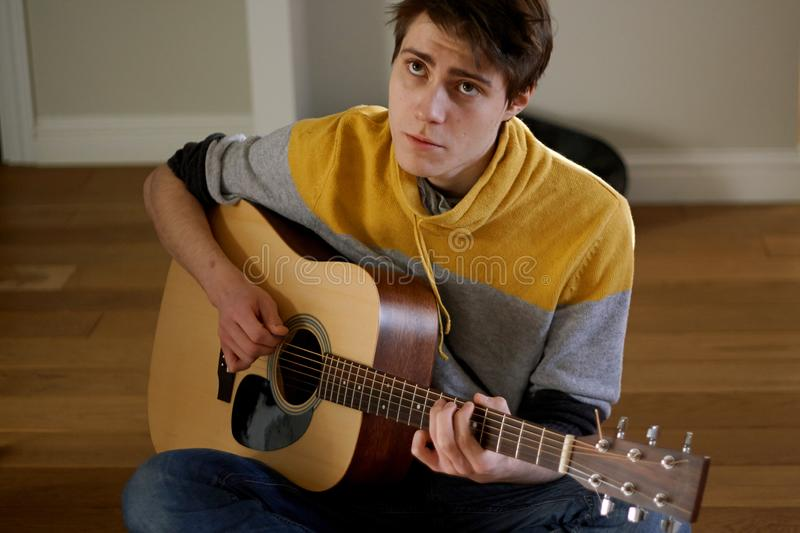 The guy  plays the guitar and sings a sad song. The guy in the yellow sweater plays the guitar and sings a sad song, sitting at home stock photo