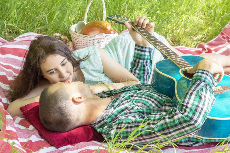 The guy plays the guitar to girlfriend. romantic meeting. summer picnic couple laying on the grass royalty free stock photography