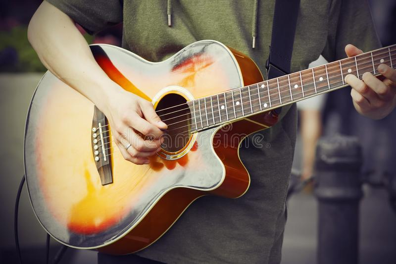 A guy plays with a mediator on a acoustic guitar stock photography