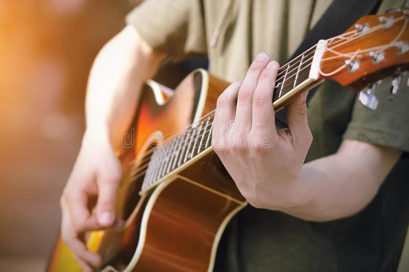 The guy plays an orange acoustic six-string guitar stock images