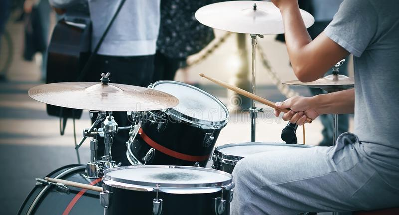 A guy plays on a red and black drum set with wooden sticks. A guy in gray clothes plays on a red and black drum set with wooden sticks, speaking at a stock photography