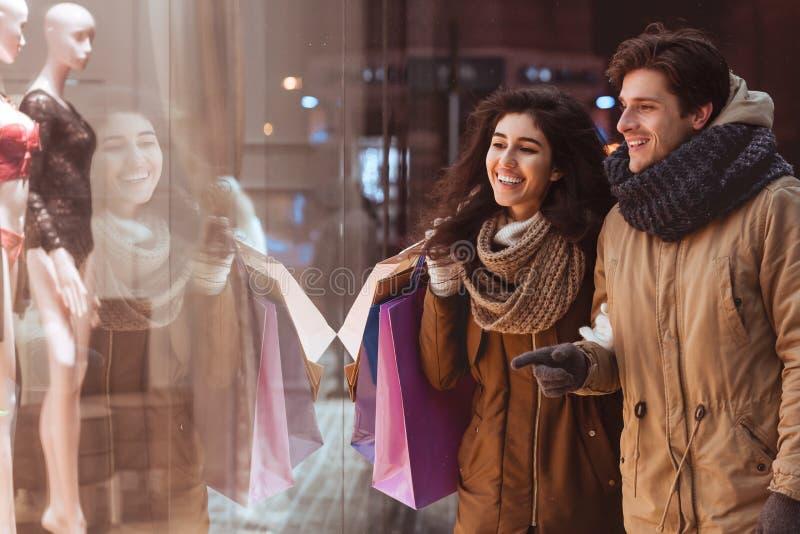 Guy Pointing beim Shopwindow Walking mit Freundin in der nächtlichen Stadt lizenzfreie stockfotos