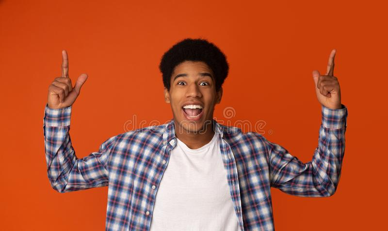 Guy Pointing Upwards adolescente alegre e vista da câmera imagem de stock royalty free