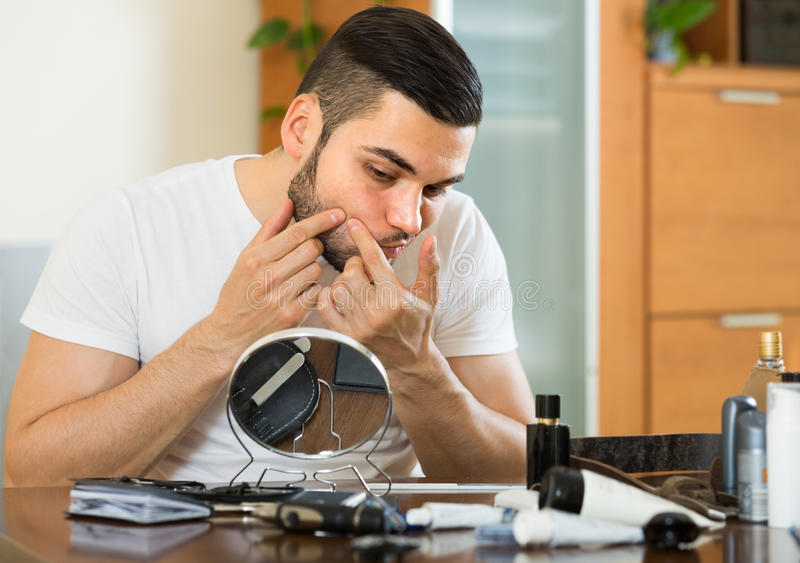 Guy popping a pimple stock image