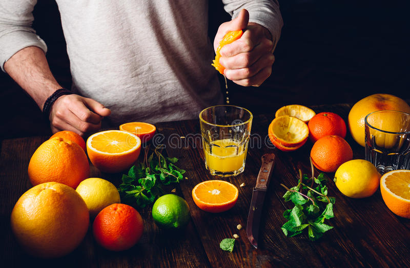 Guy Prepare el cóctel de la fruta cítrica foto de archivo