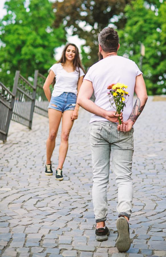 Guy prepared surprise bouquet for girlfriend. Gentlemans manners. Man hides flower bouquet behind back while wait girl. Romantic date. Couple meeting for date stock photography