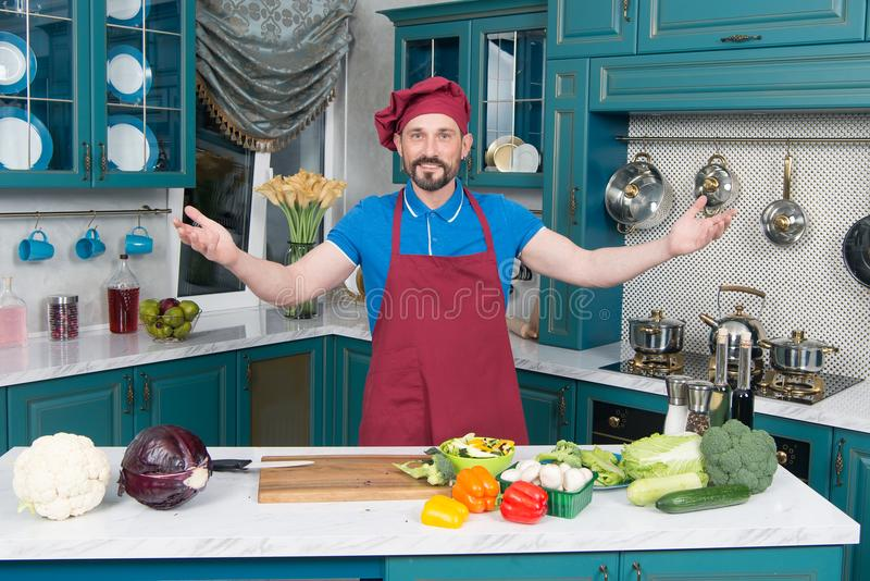 Guy welcomes to kitchen. Handsome cook invites to cooking vegetables. Man0prepared vegetables for cooking with love. stock photos