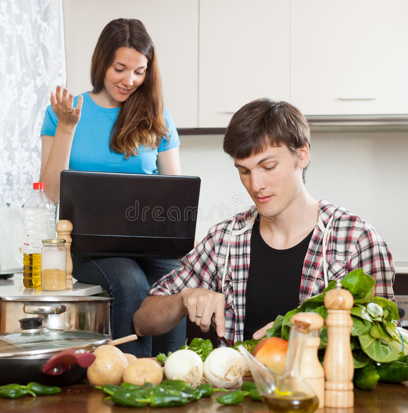 Guy and pretty girl cooking. Guy and pretty girl looking at notebook during cooking food royalty free stock photo