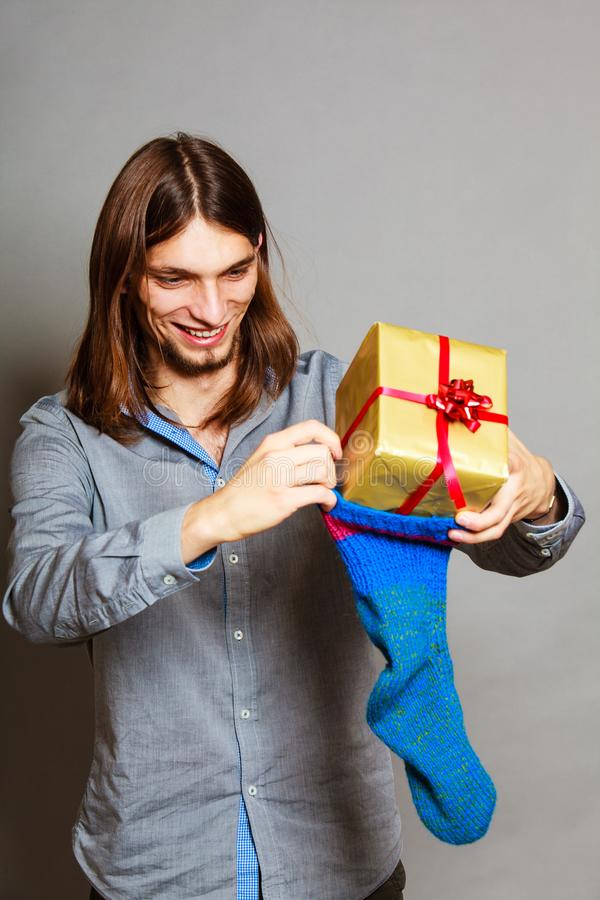 Guy putting wrapped gift in knitted christmas sock. Holiday, xmas winter time season. Stylish guy putting wrapped gift in knitted christmas sock royalty free stock images