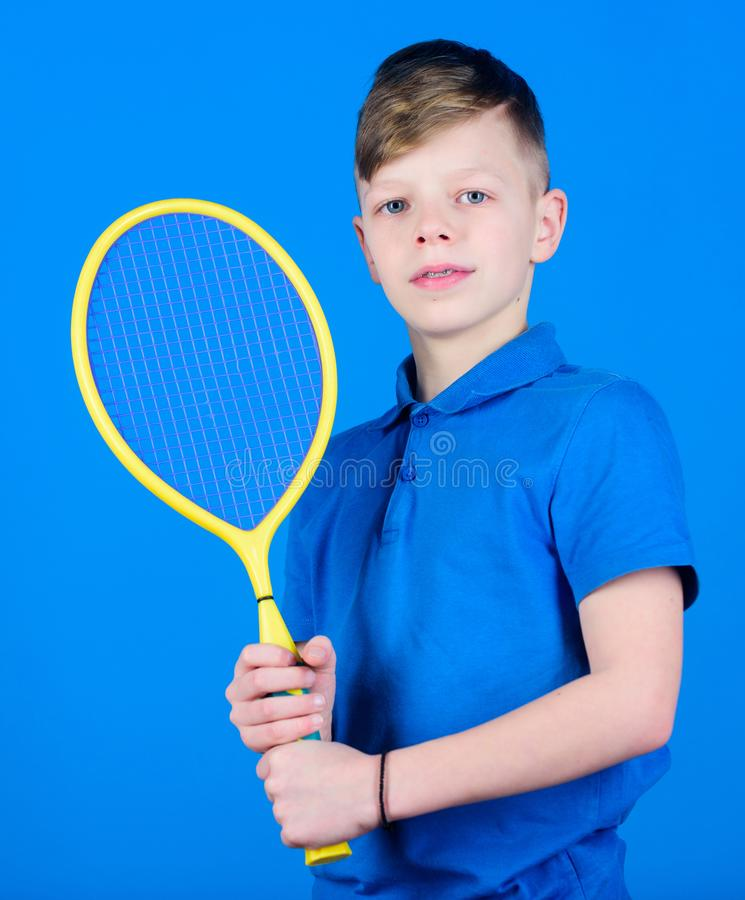 Guy with racket enjoy game. Future champion. Dreaming about sport career. Athlete kid tennis racket on blue background. Tennis sport and entertainment. Boy stock photos