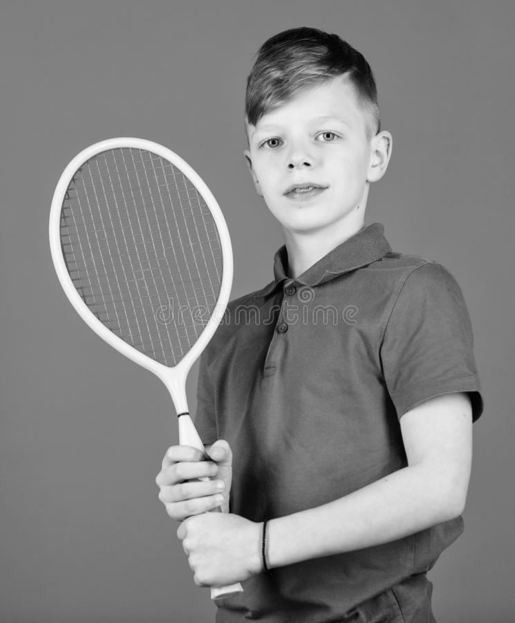 Guy with racket enjoy game. Future champion. Dreaming about sport career. Athlete kid tennis racket on blue background. Tennis sport and entertainment. Boy stock photo