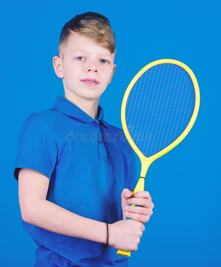 Guy with racket enjoy game. Future champion. Dreaming about sport career. Athlete kid tennis racket on blue background. Tennis sport and entertainment. Boy stock image