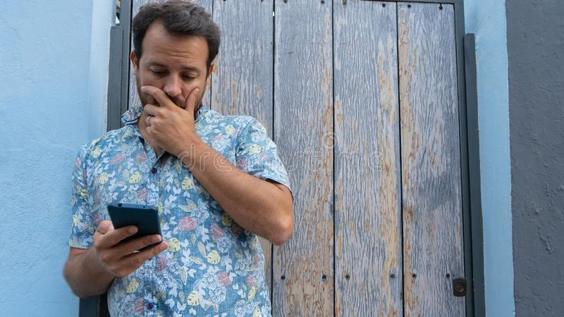Guy reading news upset with facial frustration and concerned. Modern bearded Man nervous looking smart phone watching lottery and. Hand in mouth. Scared stock images